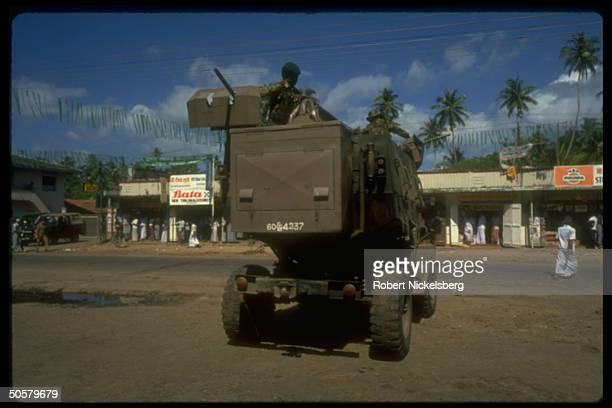 Heavily armed soldiers sit on top of an armored vehicle, rollinng down the street.