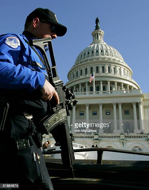 A heavily armed US Capitol Police officer patrols the west front of the US Capitol as construction workers prepare the site for US President George W...