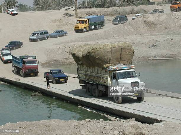 CONTENT] A heavily loaded hay truck slowly crosses the temporary pontoon bridge built by the US Navy Seebees The nearby modern bridge over the Diyala...