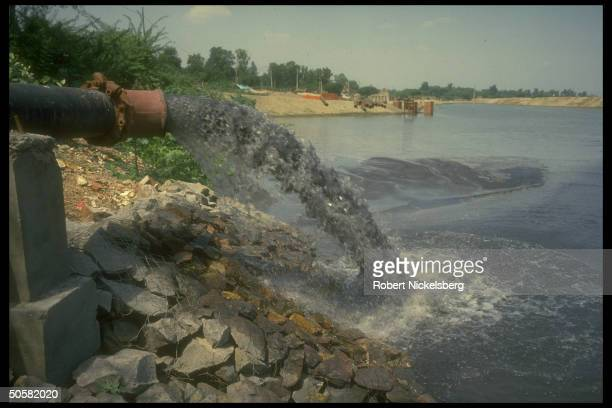 Heavily polluted Ganges River w prob contaminated water spewing fr pipe emptying into river