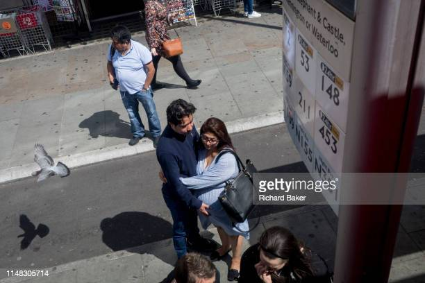 A heavily pregnant mothertobe with her doting partner stands at the bus stop opposite St Thomas's Hospital on 5th June 2019 in London England