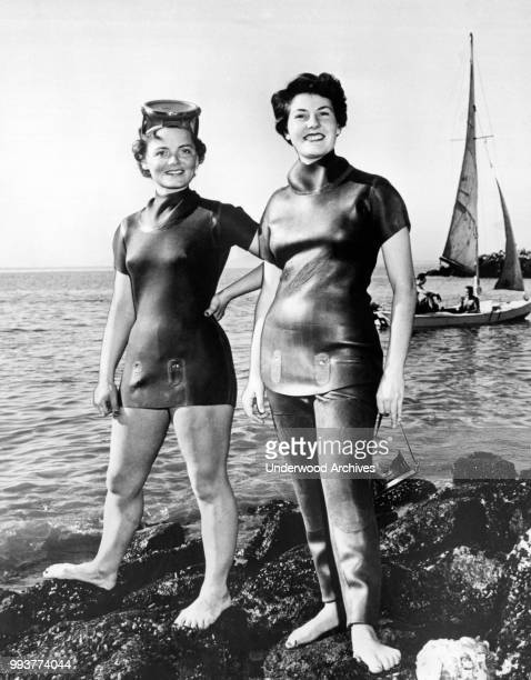 Heavily retouched photo features two unidentified women as they model neoprene wetsuits on a rocky beach Berkeley California March 1954