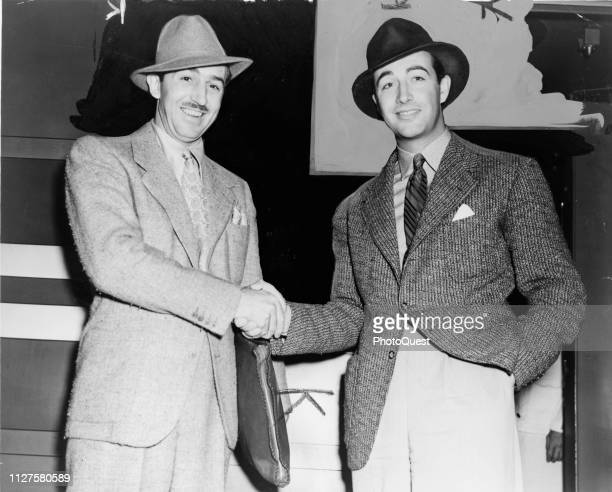 Heavily retouched portrait of American filmmaker and animator Walt Disney and actor Robert Taylor as they shake hands 1938