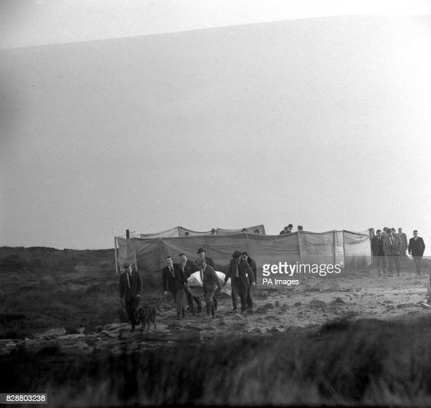 Heavily swathed in plastic sheeting human remains are carried from the screened grave on Saddleworth Moor near AshtonunderLyne Detective Chief...