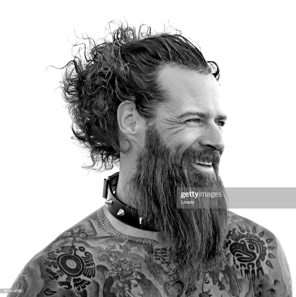 Heavily tattooed bare chested handsome male smiling in warrior stance : Stock Photo
