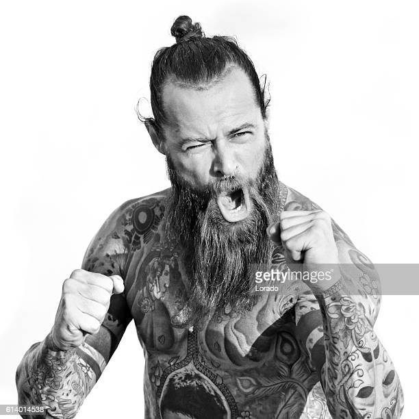 Heavily tattooed bare chested handsome male standing in fighting stance