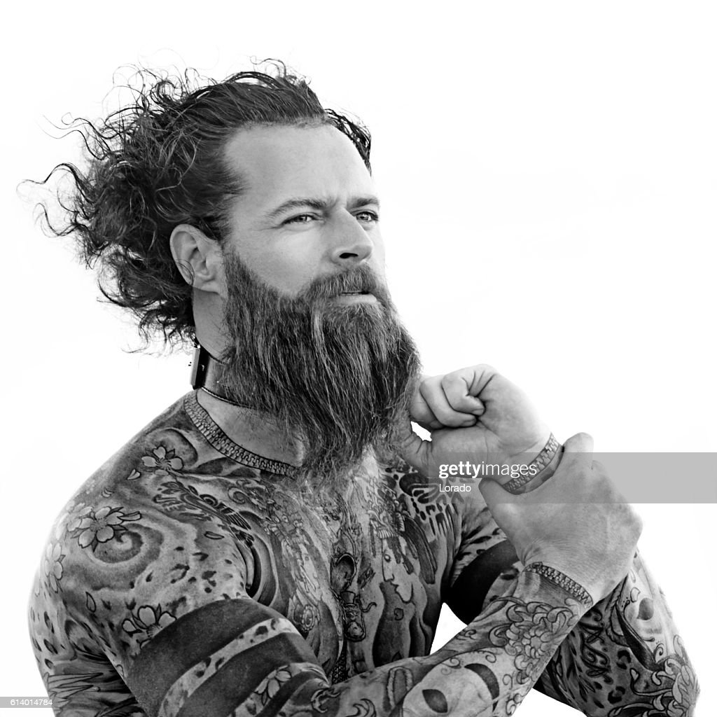 Heavily tattooed bare chested handsome male standing in warrior stance : Stock Photo