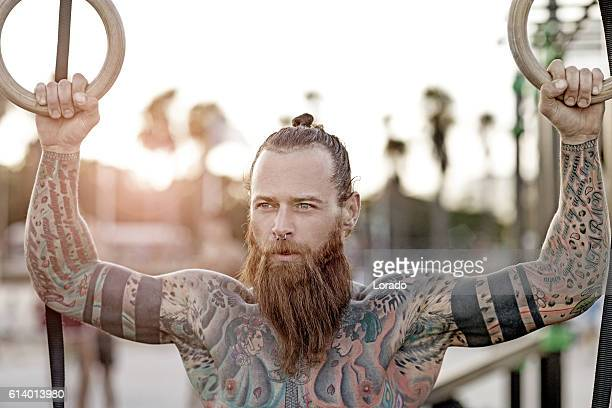 heavily tattooed bearded athletic alternative man stretching before a workout - homme poilu photos et images de collection