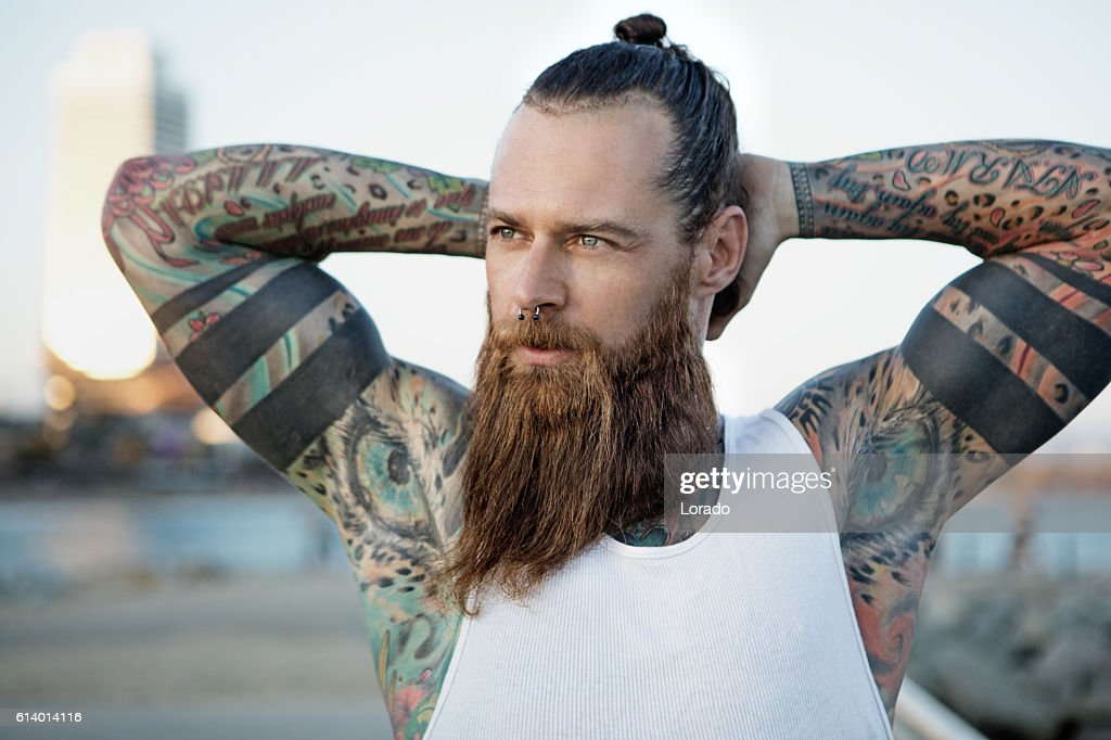 Heavily tattooed bearded athletic alternative man stretching before a workout : Stock-Foto
