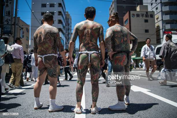 Heavily tattooed Japanese men chat in the street near Asakusa Temple on the third and final day of Sanja Festival on May 20 2018 in Tokyo Japan Sanja...