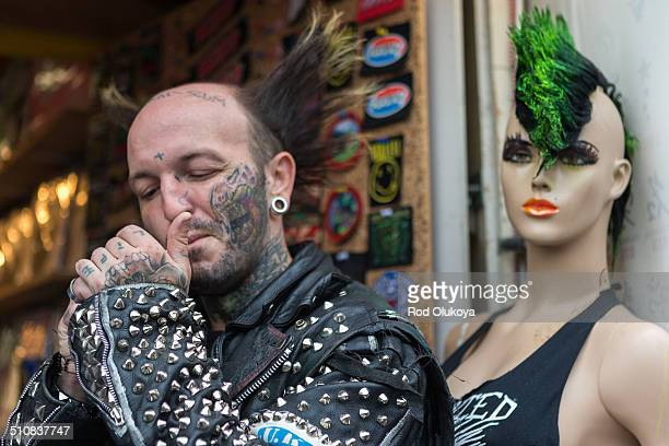 A heavily tattooed punk known as Skank lights up a cigarette just outside a store in Camden Behind him stands a beautiful mannequin that could pass...