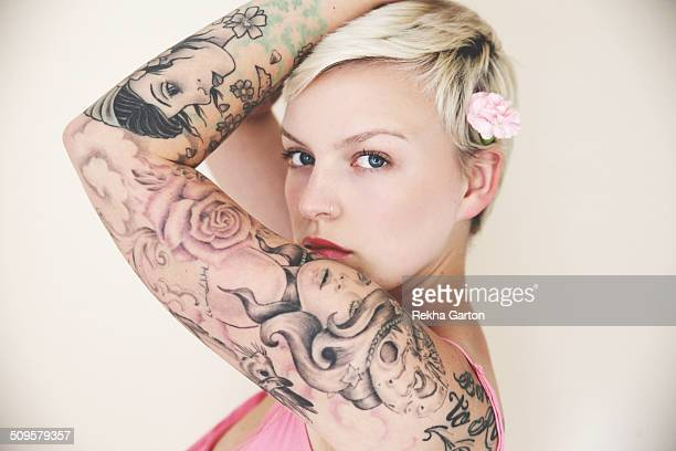 Heavily tattooed woman wearing a flower