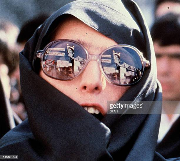 Heavily veiled Iranian woman with modern glasses in which slogans and Ayatollah Khomeini' s portrait are reflected demonstrates outside of the US...