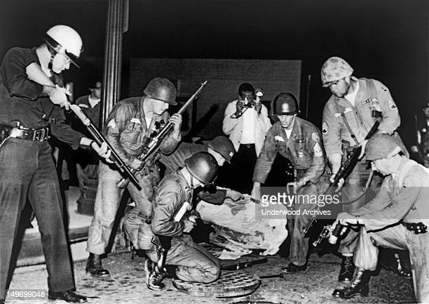 A heavilyarmed group of police and National Guardsmen stand ready at an open manhole after dropping a tear gas shell inside Los Angeles California...