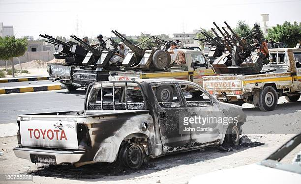 Heavilyarmed gun trucks reverse slowly up the main street past a burnt out vehicle into the west of Sirte as rebels advance on the town on October 12...