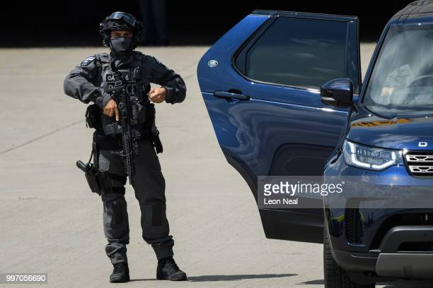A heavilyarmed member of the security details prepapres himself before Air Force One carrying US President Donald Trump and First Lady Melania...