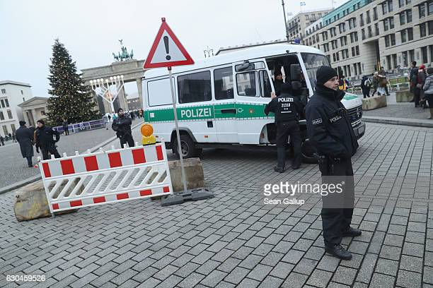 Heavilyarmed police stand at concrete security barriers near the Brandenburg Gate a popular tourist destination on December 23 2016 in Berlin Germany...