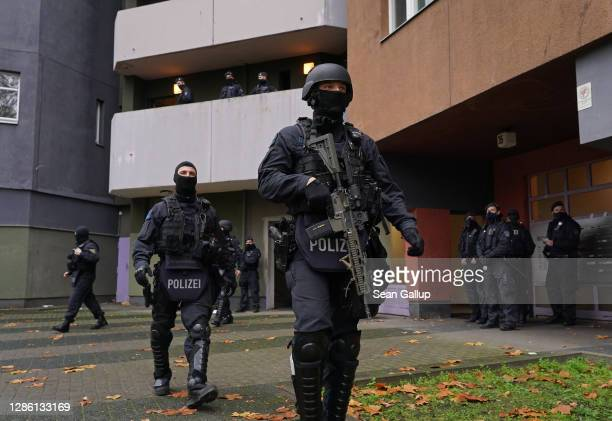 Heavily-armed police stand outside an apartment building in Kreuzberg district during raids in which police arrested three suspects in connection...