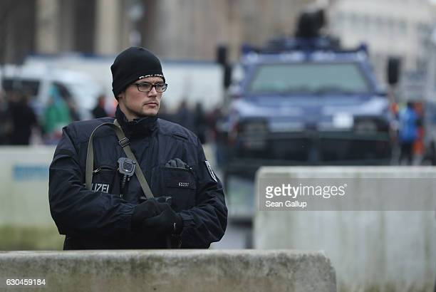 A heavilyarmed policeman stands behind concrete security barriers near a police armoured vehicle near the Brandenburg Gate prior to a concert there...