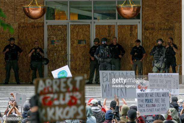 Heavilyarmed riot police stand on the porch of the damaged Portland Justice Center during the protests over the death of George Floyd an unarmed...