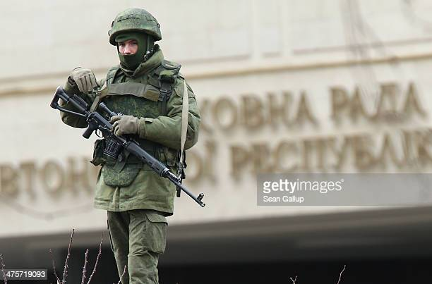 Heavily-armed soldier without identifying insignia guards the Crimean parliament building shortly after several dozen soldiers took up positions...