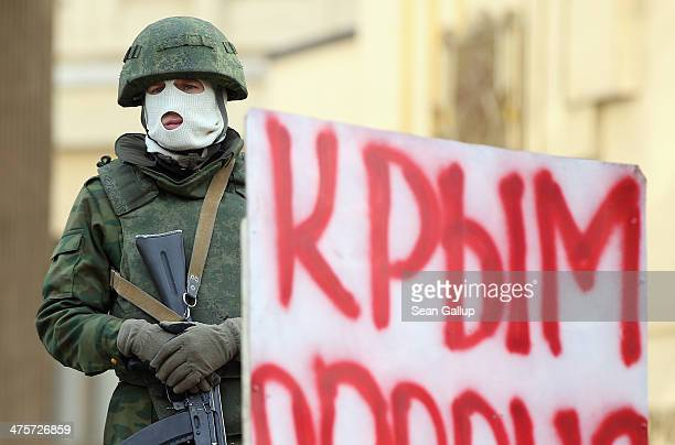 A heavilyarmed soldier without identifying insignia guards the Crimean parliament building next to a sign that reads Crimea Russia after several...