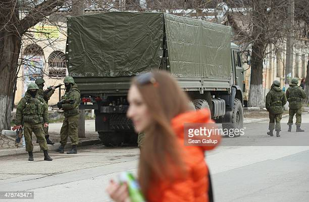 Heavily-armed soldiers displaying no identifying insignia maintain watch in a street as people walk past in the city center on March 1, 2014 in...