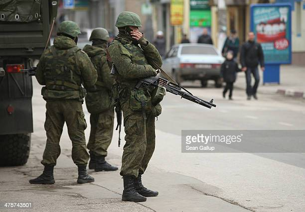 Heavilyarmed soldiers displaying no identifying insignia maintain watch in a street as people walk past in the city center on March 1 2014 in...