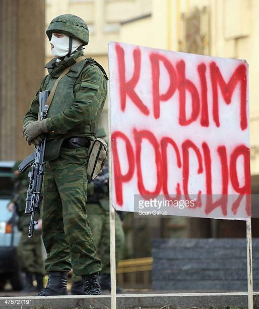 Heavilyarmed soldiers without identifying insignia guard the Crimean parliament building next to a sign that reads 'Crimea Russia' after taking up...