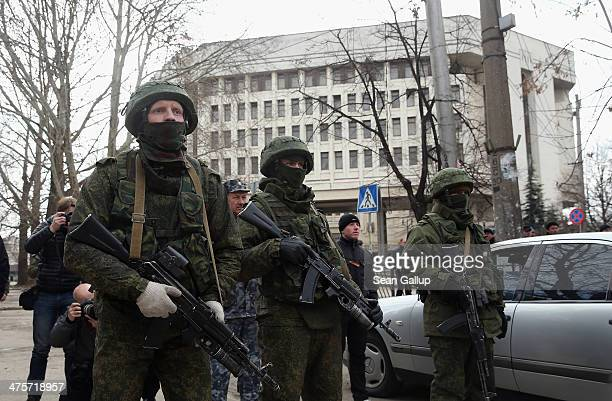 Heavily-armed soldiers without identifying insignia guarding the Crimean parliament building look on as a group of men, who moments later identifed...