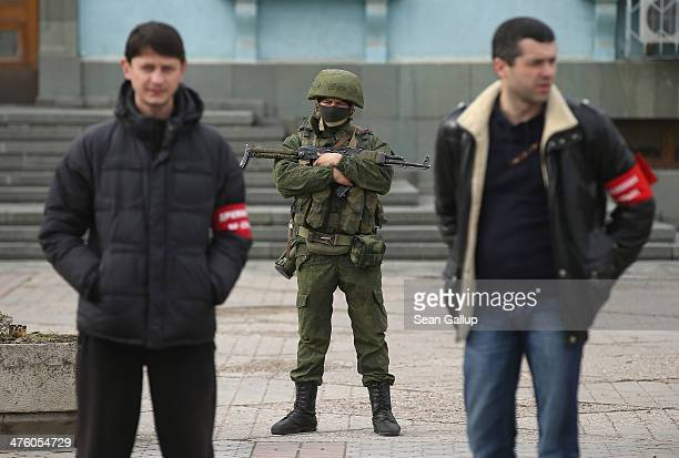 Heavilyarmed troops displaying no identifying insignia and local proRussian militants stand guard outside a local government building on March 2 2014...