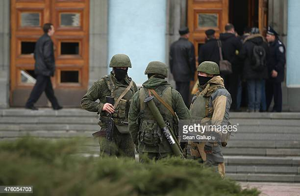 Heavily-armed troops displaying no identifying insignia and who were mingling with local pro-Russian militants stand guard outside a local government...