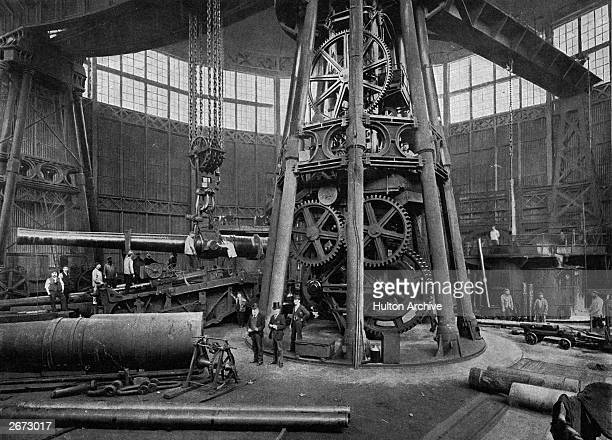A heavy breechloading gun being lowered into its place on its carriage by a powerful steam crane at the Arsenal in Woolwich
