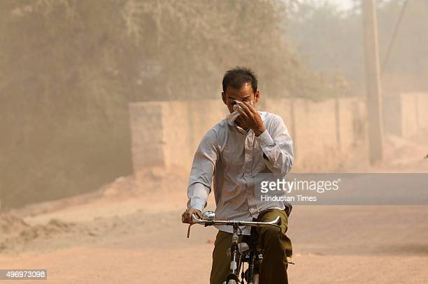Heavy dust seen as vehicles move on a road making already polluted air more worsen, as people commutes through a bad road, on November 13, 2015 in...