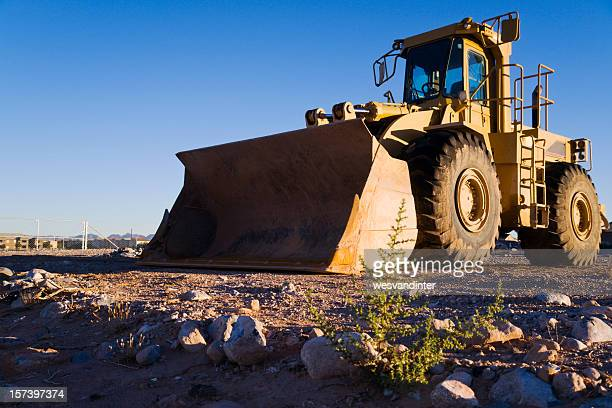 Heavy duty hydraulic front end loader in empty field