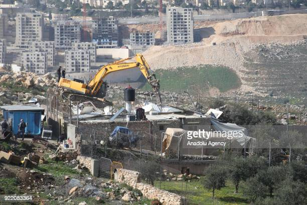 A heavy duty machine that belongs to Israeli forces demolishes a Palestinian family's house with the claim of being unlicensed in the Shuafat...