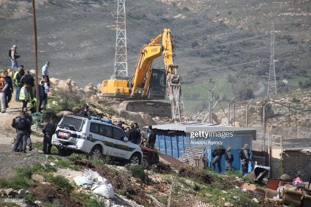 A heavy duty machine that belongs to Israeli forces demolishes a Palestinian family's house with the claim of being unlicensed as Israeli soldiers stand guard in the Shuafat neighborhood, Eastern Jerusalem on February 21, 2018.