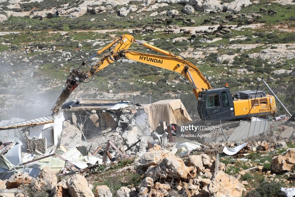 A heavy duty machine that belongs to Israeli forces demolishes a Palestinian family's house with the claim of being unlicensed in the Shuafat neighborhood, Eastern Jerusalem on February 21, 2018.