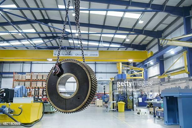 heavy engineering gear hanging from crane in factory - oggetti pesanti foto e immagini stock