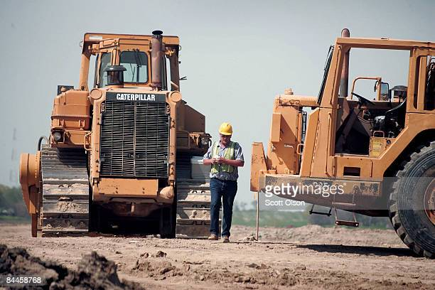 A heavy equipment operator walks between Caterpillar earth moving equipment at a road construction site on April 24 2006 near Joliet Illinois...