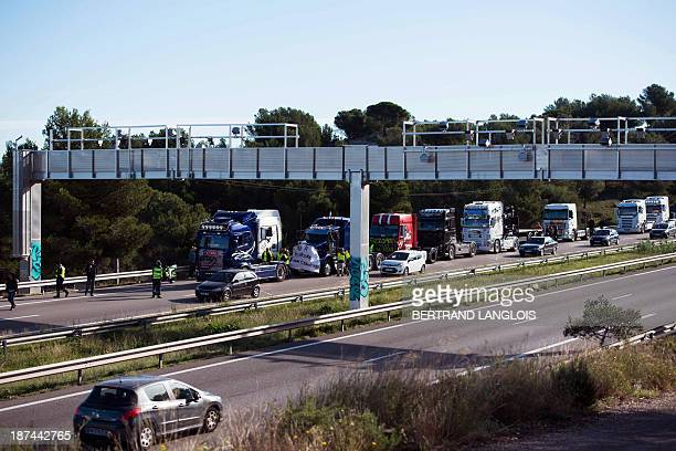 Heavy goods vehicles drivers demonstrate against the Ecotaxe entironmental tax on the A55 highway next to a bridge with radars set up to collect the...