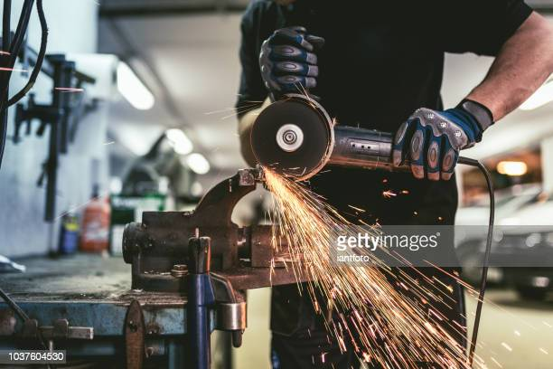 heavy industry worker cutting steel with an angle grinder. - cutting stock pictures, royalty-free photos & images