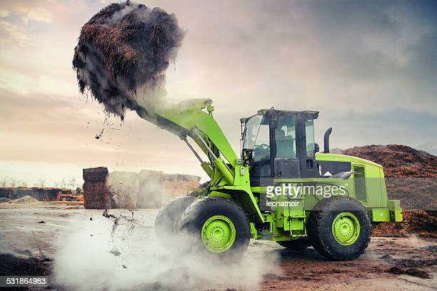 Heavy loader machinery carrying mushroom compost