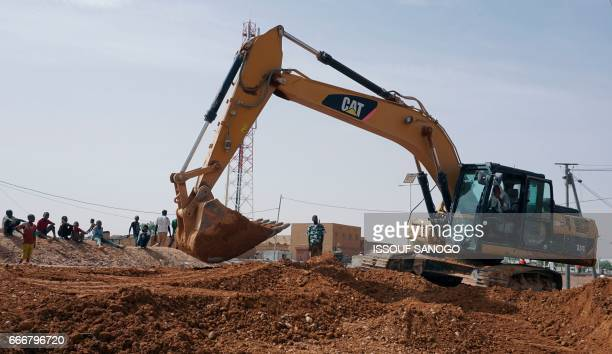 Heavy machinery are used in the laying of a road in the city of Agadez central Niger on April 6 2017 / AFP PHOTO / ISSOUF SANOGO
