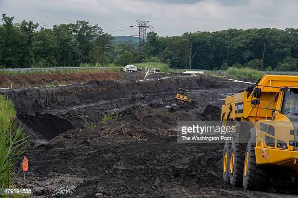 Heavy machinery excavate and carry coal ash from drained coal ash pond E at Possum Point Power Station in Dumfries Va on June 26 2015 Dominion...