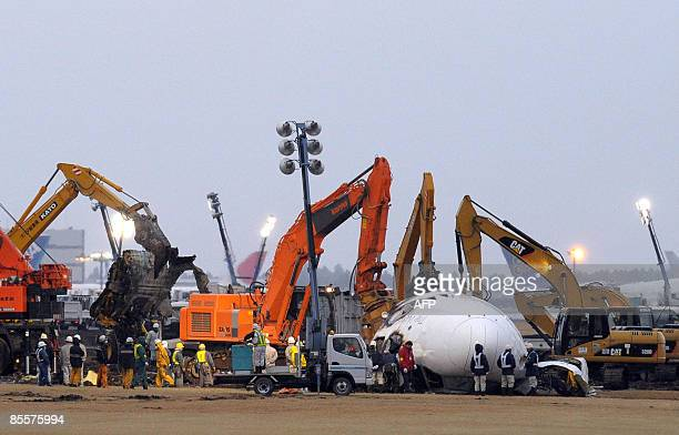 Heavy machinery is used to remove the burnt out body of a FedEx cargo plane at the Narita International Airport early on March 24 2009 in Narita...