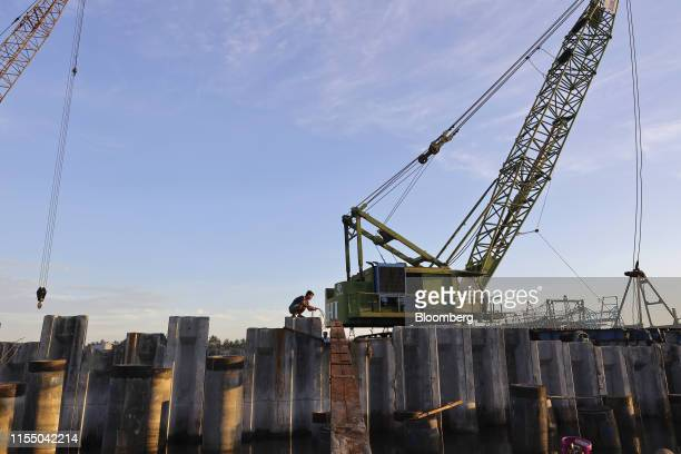 Heavy machinery stand near pylons for a pier under construction at Tan Quang harbor in Quang Nam province Vietnam on Wednesday June 26 2019 Fishermen...