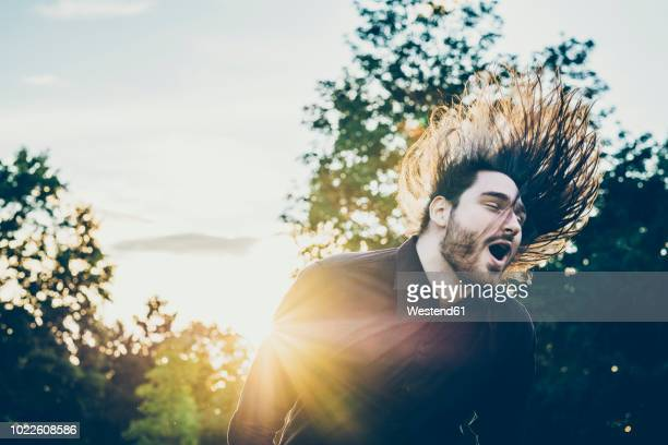 heavy metal fan headbanging in a park - heavy metal stock pictures, royalty-free photos & images