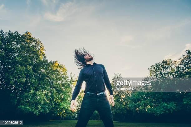 heavy metal fan headbanging in a park - heavy metal stock-fotos und bilder