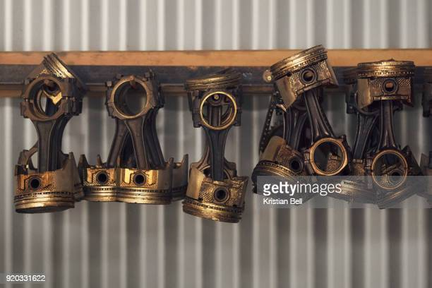 heavy old vehicle pistons hanging from a corrugated shed wall - piston stock pictures, royalty-free photos & images